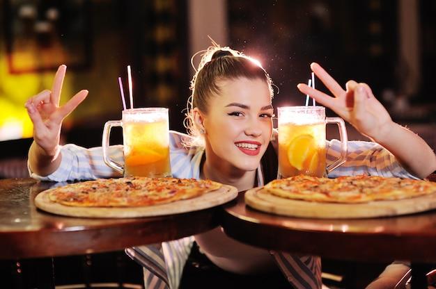 Menina bonita comendo pizza e bebendo cerveja ou um cocktail de cerveja cítrica de um bar ou pizzaria. Foto Premium