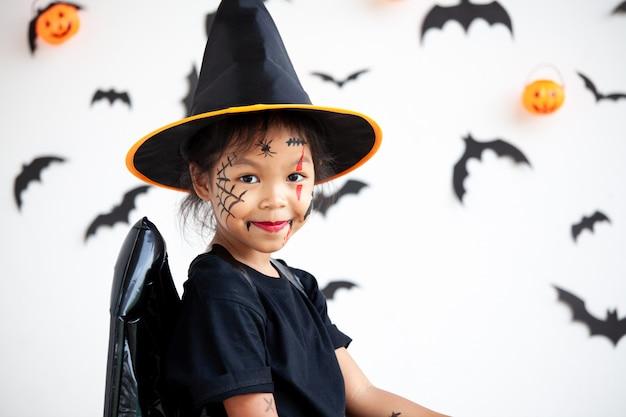 Menina bonita criança asiática vestindo maquiagem e trajes de halloween se divertindo na celebração do dia das bruxas Foto Premium