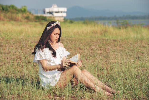 Menina bonita da ásia no campo de grama, lendo um livro coberto Foto Premium