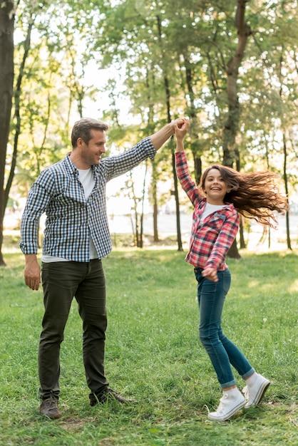 Menina bonita dançando com o pai na terra gramada no parque Foto gratuita
