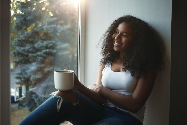 Menina bonita, de aparência mestiça, segurando uma caneca grande e olhando pela janela com um sorriso alegre, vendo algo agradável lá fora, tomando chá ou café. pessoas e estilo de vida Foto gratuita