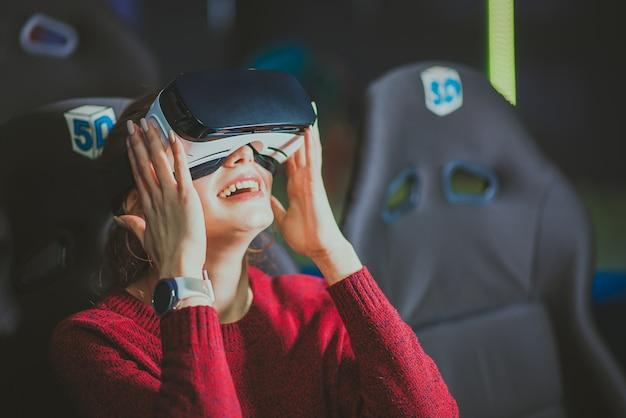 Menina bonita de óculos virtuais está assistindo a um filme com efeitos especiais Foto Premium