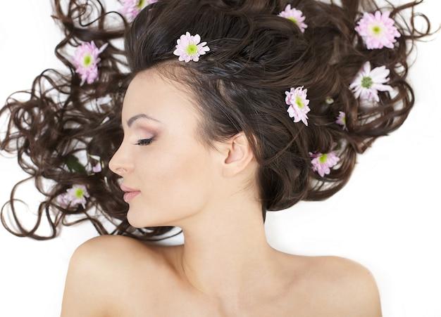 Menina bonita, deitado com flores brilhantes em sua maquiagem brilhante cabelo isolada no branco Foto gratuita