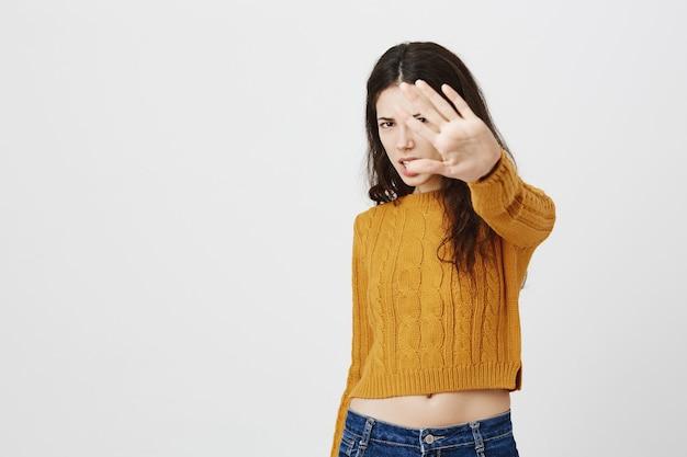 Menina bonita descontente e incomodada estende a mão para rejeitar ou parar de fotografar, não gosta de tirar fotos de si mesma Foto gratuita
