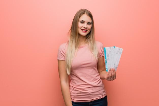 Menina bonita do russo alegre e com um grande sorriso. ela está segurando passagens aéreas. Foto Premium