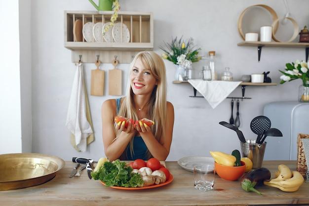 Menina bonita e alegre em uma cozinha com legumes Foto gratuita