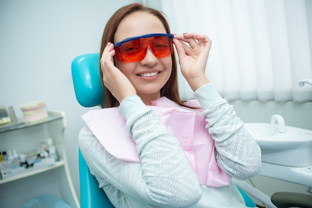 Menina bonita e alegre na cadeira do dentista. tratamento dentário. clinica odontológica Foto Premium