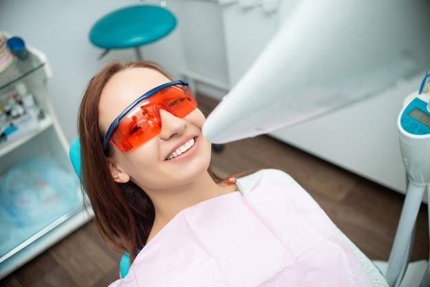 Menina bonita e alegre na cadeira do dentista Foto Premium