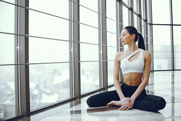 Menina bonita e elegante, fazendo yoga Foto gratuita