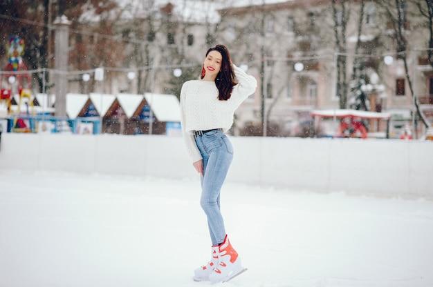 Menina bonita e linda com um suéter branco em uma cidade de inverno Foto gratuita