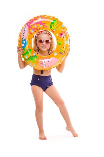Menina bonita em biquíni listrado vermelho, fundos azuis, óculos escuros e grinalda rosa ficar com anel de borracha na mão Foto Premium