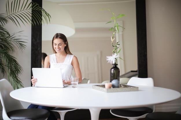 Menina bonita em casa trabalhando em um laptop Foto Premium