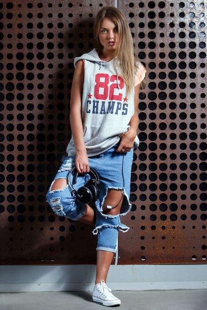 Menina bonita em jeans rasgados Foto gratuita