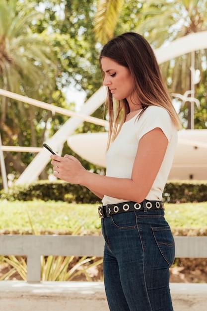 Menina bonita em jeans, verificando o smartphone Foto gratuita