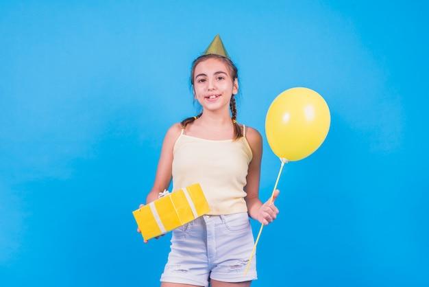 Menina bonita em pé com caixa de presente e balões no papel de parede azul Foto gratuita