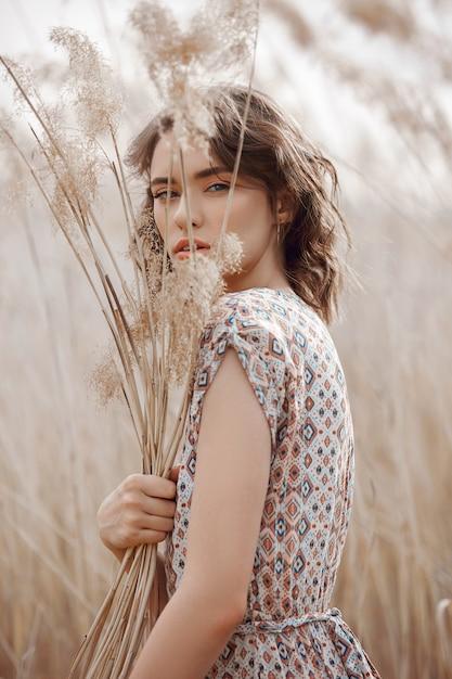 Menina bonita em um campo com grama alta no outono. retrato da arte de uma mulher Foto Premium