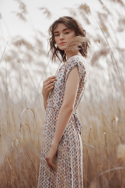 Menina bonita em um campo com grama alta no outono. Foto Premium