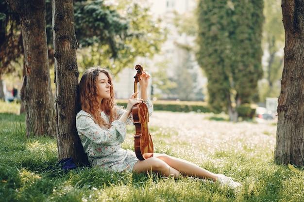 Menina bonita em um parque de verão com um violino Foto gratuita