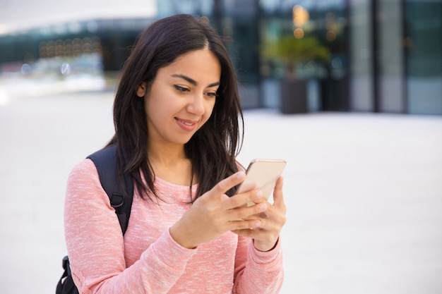 Menina bonita estudante de conteúdo usando smartphone Foto gratuita