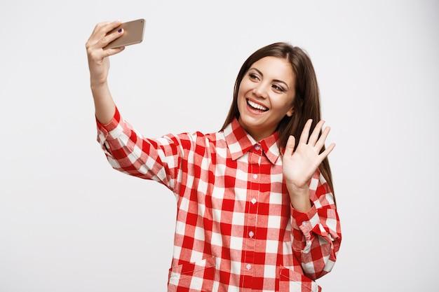 Menina bonita, fazendo chamadas de vídeo com os amigos, acenando com a mão esquerda Foto gratuita