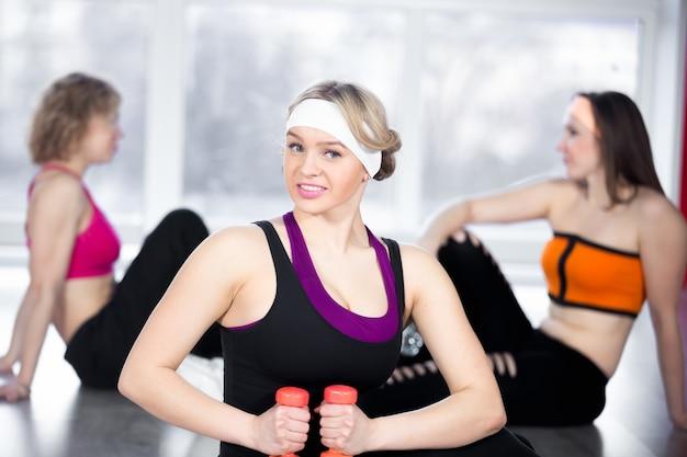 Menina bonita fazendo exercícios físicos com dumbbells em sala de aula Foto gratuita