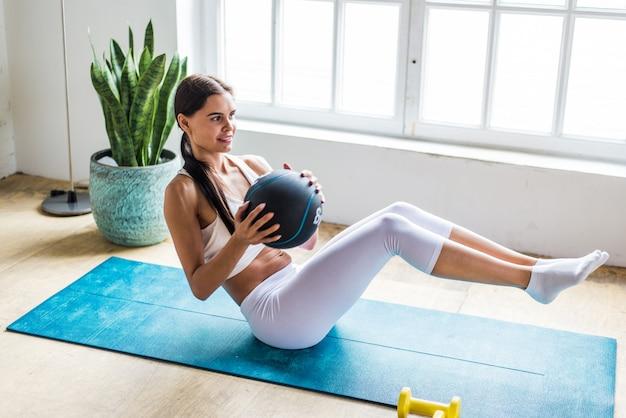 Menina bonita, fazendo treinamento e yoga em casa pela manhã Foto Premium