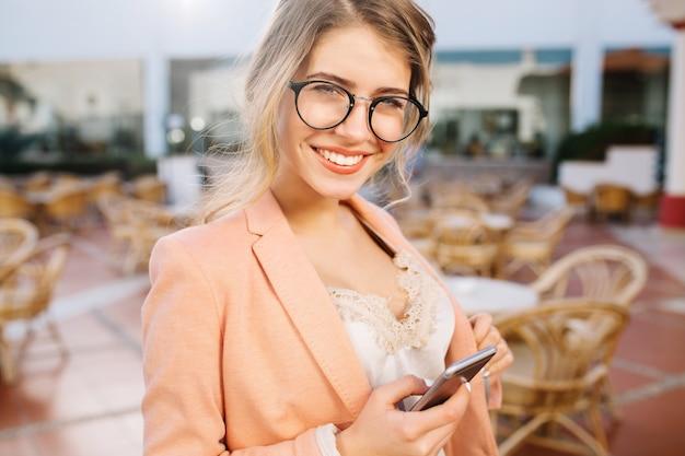 Menina bonita feliz com smartphone cinza na mão, sorridente, estudante, mulher de negócios. café de rua, terraço. usando óculos elegantes, jaqueta rosa, blusa de renda bege. Foto gratuita