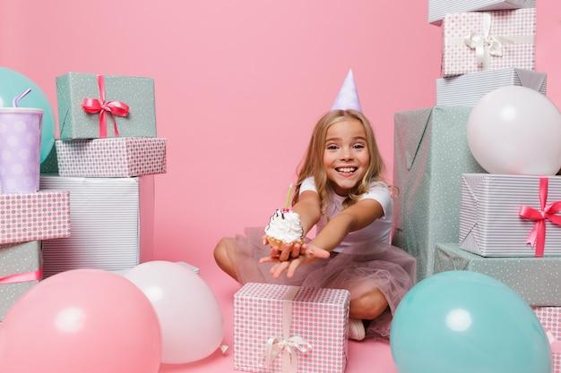 Menina bonita feliz em um chapéu de aniversário comemorando Foto gratuita