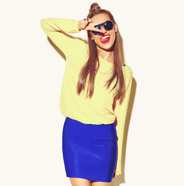 Menina bonita feliz sorridente mulher morena bonita em roupas de verão casual colorido hipster amarelo com lábios vermelhos isolados no branco mostrando sinal de paz e a língua Foto gratuita