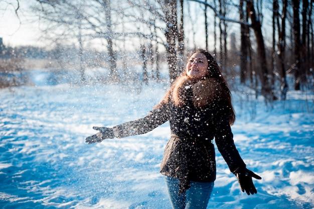 Menina bonita joga neve em um parque de inverno Foto Premium