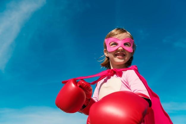 Menina bonita jogando super-herói Foto gratuita