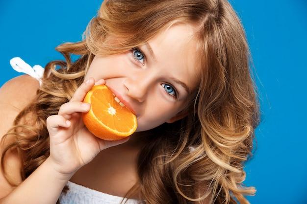 Menina bonita jovem comendo laranja sobre parede azul Foto gratuita