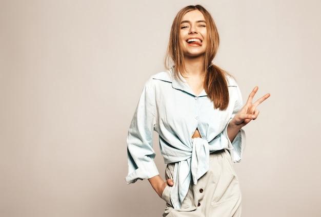 Menina bonita jovem em roupas de verão casual. modelo engraçado positivo. mostrando a língua e o símbolo da paz Foto gratuita