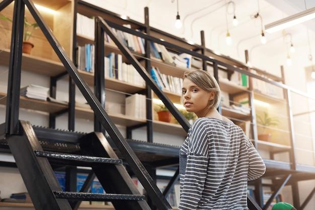 Menina bonita jovem estudante loira com cabelo curto em camisa listrada casual, passar um tempo na biblioteca moderna depois da universidade, preparando-se para os exames com os amigos. garota de pé perto da escada vai levar Foto gratuita