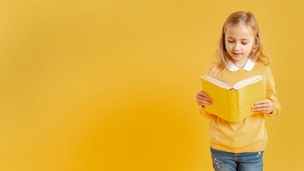 Menina bonita lendo com cópia-espaço Foto gratuita