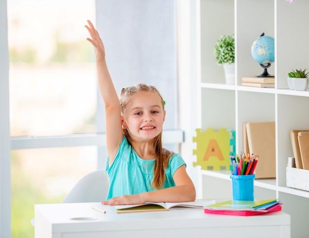 Menina bonita levantou a mão na sala de aula Foto Premium