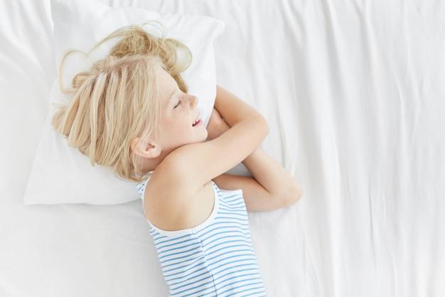 Menina bonita loira na camiseta de marinheiro, deitado no travesseiro branco, sorrindo enquanto dorme enquanto vê sonhos agradáveis. criança do sexo feminino repousante dormindo após um dia difícil, brincando com seus amigos. crianças, relaxamento Foto gratuita