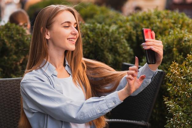 Menina bonita loira tomando selfies Foto gratuita