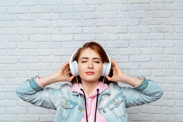 Menina bonita moda legal ouvindo música em fones de ouvido Foto Premium