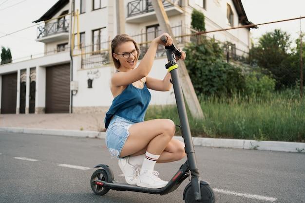 Menina bonita, montando uma scooter elétrica no verão na rua Foto gratuita