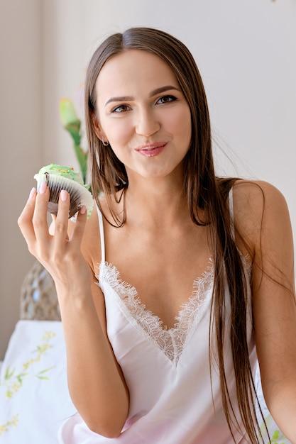 Menina bonita, morder o bolo enquanto tomando café da manhã na cama Foto Premium