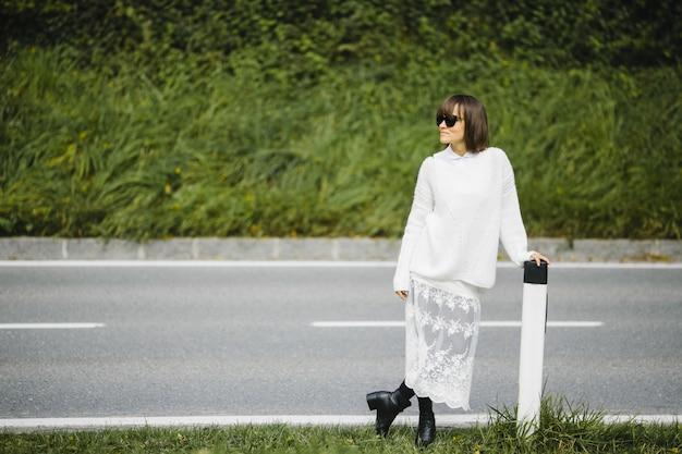 Menina bonita morena em pé ao lado da estrada Foto gratuita