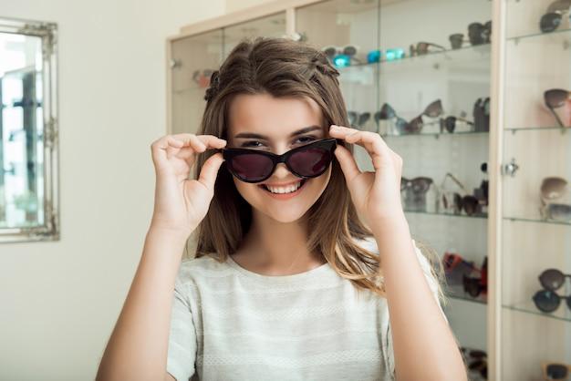 Menina bonita morena sorrindo, experimentando óculos de sol na loja de óptica Foto gratuita