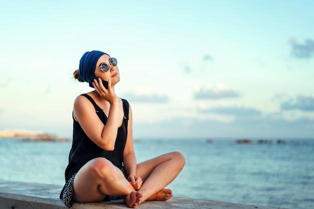 Menina bonita morena turista fala por telefone ao ar livre Foto Premium