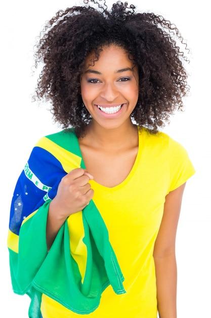 Menina bonita na camiseta amarela segurando bandeira brasileira sorrindo para a câmera Foto Premium