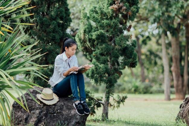 Menina bonita na floresta de outono, lendo um livro Foto gratuita