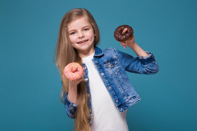 Menina bonita na jaqueta jeans com longos cabelos castanhos segurar doughnust Foto Premium