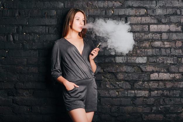Menina bonita na moda fumando um cigarro sem tabaco, exalando grandes nuvens de fumaça. vestida com roupas da moda. Foto Premium