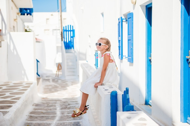 Menina bonita na rua da aldeia tradicional grega tradicional em mykonos Foto Premium