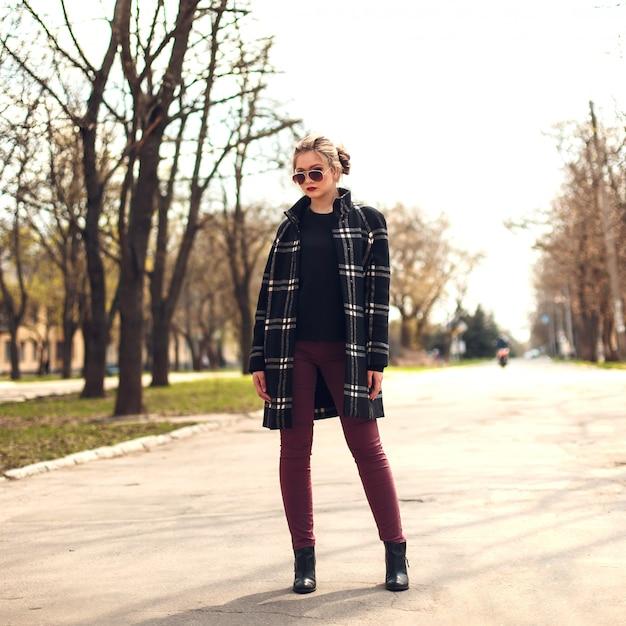 Menina bonita no casaco xadrez e óculos de sol em pé em um strreet Foto Premium